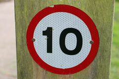 10 mph warning sign. 10 mph speed restriction vehicle warning sign on a wooden post background in a park with grass to the right and road to the left Royalty Free Stock Images