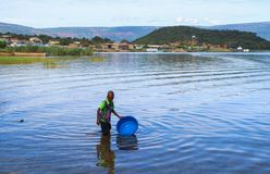 A black boy draws water in a blue basin from Lake Tanganyika stock photo