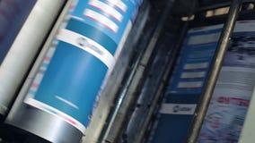 A máquina de impressão passa o papel através dos cilindros filme
