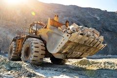 Máquina del cargador de la rueda que descarga rocas Fotografía de archivo libre de regalías
