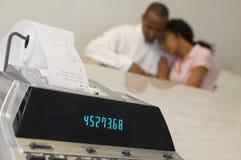 Máquina do recibo da despesa com pares no fundo Fotografia de Stock