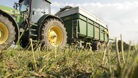 Máquina segadora con el tractor remolque que cosecha el heno metrajes