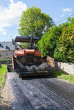 Máquina tarring del camino usando el asfalto de la mezcla preparada de antemano con las aletas delanteras abiertas Imágenes de archivo libres de regalías