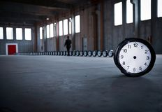 Mr Black and the clocks. A man, dressed in black, is walking next to fifty clocks toward a red door, in an empty factory. A clock without hands in the foreground stock photography