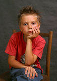 Mr. Calmness. The boy in a red vest sitting on a chair Stock Photo
