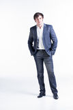 Mr. Confident. Portrait of a young business man wearing a gray suit standing confidently with his hands in his pockets Royalty Free Stock Photos