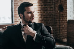 Mr. Handsome. Close up thoughtful young handsome man in formalwear and bow tie looking away and adjusting his bow tie while sitting in a chair in loft interior Royalty Free Stock Image