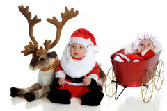 Mr. and Mrs. Claus. An adorable baby santa with his reindeer with baby Mrs. Claus in a wagon nearby. Isolated on white stock photography