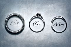 Mr And Mrs Depicted In Rings. Text of Mr & Mrs depicted within the circle of engagement and wedding rings on grey textured background stock image