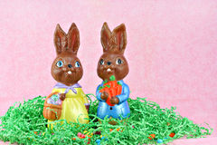Mr. and Mrs. Easter Bunny Figures. Mr. and Mrs. Easter Bunny standing on a bed of easter grass and jelly beans. Handmade and homemade in chocolate brown stock photo