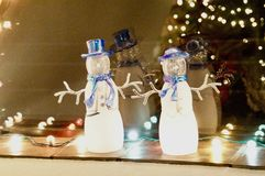 Mr. & Mrs. Frosty Snowman Christmas Window Reflection Display. Snow people, Christmas Lights and their reflections in window display with Christmas tree and royalty free stock photos