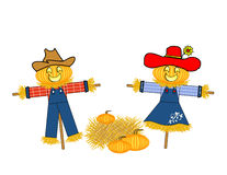 Mr. and Mrs. Pumpkin Scarecrow. Scarecrows dressed as a man and a woman with carved pumpkin heads separated by a bale of hay and pumpkins Royalty Free Stock Photo