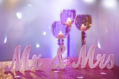 Mr. & Mrs. with Purple Goblet Candle Holders. And purple bokeh light background royalty free stock photography