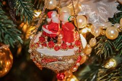 Mr and Mrs Santa kissing retro really old Christmas decoration of colloid and styrofoam and beads and trim hanging from a tree -