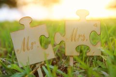 Mr and Mrs sign. Two puzzle pieces placed in the grass during sunset time. harmony and wedding concept. royalty free stock photo