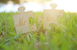 Mr and Mrs sign. Two puzzle pieces placed in the grass during sunset time. harmony and wedding concept. Mr and Mrs sign. Two puzzle pieces placed in the grass stock images