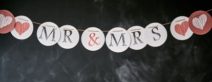 Mr and Mrs wedding garland panoramic banner. With individual letters and hearts on circles over a grunge chalkboard background with copy space stock photography