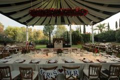 MR and MRS wood chairs for bride and groom couple at wedding decoration with luxury wedding awning decorated with natural roses. And flowers, elegant wedding stock photos