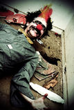 Mr Sleepy The Creepy Clown. Lays On A Holey Rubbish Littered Floor With A Horrific Smile Across His Frightening Face Royalty Free Stock Photos