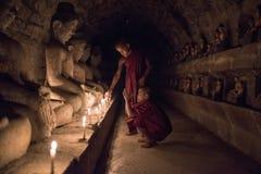Mrauk U,缅甸- DEC 15日2014年:祈祷与加州的年轻初学者 免版税库存图片