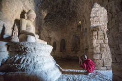 Mrauk U, MYANMAR - DEC 13, 2014: Young  neophyte praying in a Bu Royalty Free Stock Image