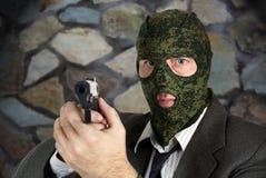 Mördaren i kamouflagemaskering siktar med en pistol Arkivbilder
