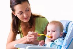Mère alimentant la chéri affamée Image stock