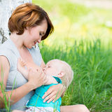 Mère allaitant un bébé en nature Photo stock
