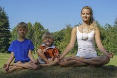 Mère avec des enfants méditant sur l'herbe verte Images stock