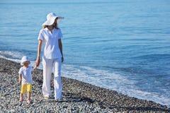 Mère avec la promenade d'enfant sur le bord de la mer Photographie stock