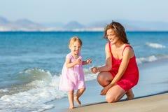Mère avec le petit descendant sur la plage Photographie stock libre de droits
