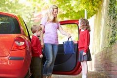 Mère conduisant à l'école avec des enfants Image stock