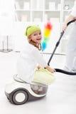 Mère de aide de petite fille pour nettoyer la salle Photographie stock