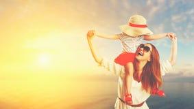 Mère de famille et fille heureuses d'enfant sur la plage au coucher du soleil Image stock
