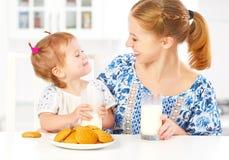 Mère de famille et fille heureuses de fille de bébé au petit déjeuner : biscuits avec du lait Photographie stock libre de droits