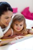 Mère de soin affichant un livre avec sa fille Photo stock