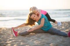Mère en bonne santé et bébé s'étirant sur la plage Image libre de droits