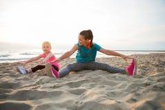 Mère en bonne santé et bébé s'étirant sur la plage Images libres de droits