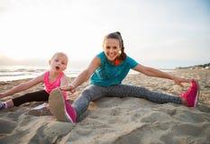 Mère en bonne santé et bébé s'étirant sur la plage Photographie stock libre de droits