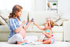 Mère enceinte de famille heureuse et fille d'enfant préparant le clothi Image stock