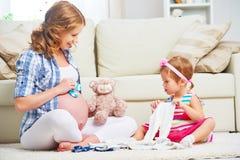 Mère enceinte et enfant de famille heureuse préparant l'habillement pour le Ne Images stock
