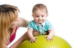 Mère et bébé ayant l'amusement avec la boule gymnastique Photos libres de droits