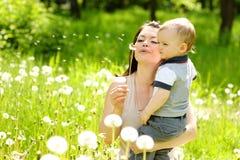 Mère et bébé garçon soufflant sur un pissenlit Photo stock