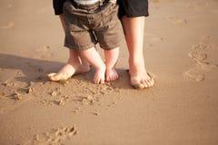 Mère et chéri marchant sur la plage Photographie stock libre de droits