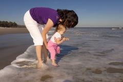 Mère et descendant jouant à la plage Image libre de droits