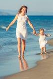 Mère et descendant marchant sur la plage Image libre de droits