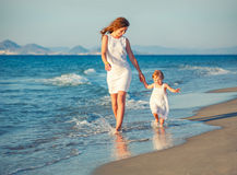 Mère et descendant marchant sur la plage Photos stock