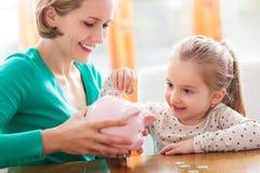 Mère et descendant mettant des pièces de monnaie dans la tirelire Image stock