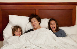 Mère et deux filles dans le lit Photo stock