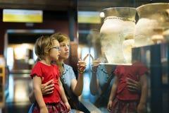 Mère et enfant semblant de vieux amphores dans le musée Image libre de droits